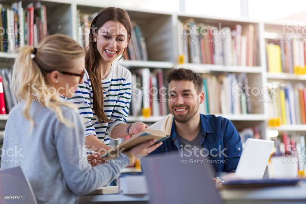 University students working in the library at campus stock photo