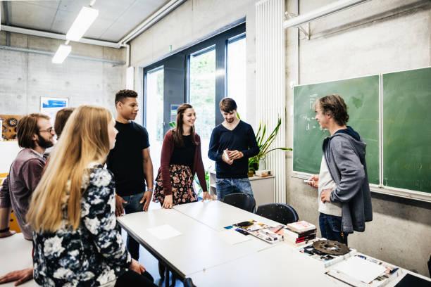 Universität Tutor im Gespräch mit Studenten vor Blackbaord – Foto