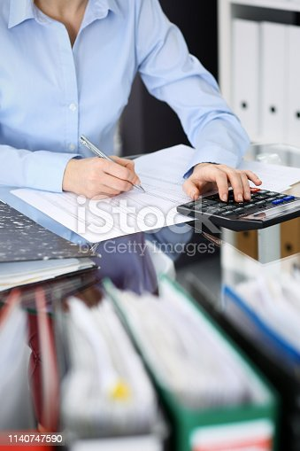 istock Unknown bookkeeper woman or financial inspector  making report, calculating or checking balance, close-up. Business portrait. Audit or tax concepts 1140747590