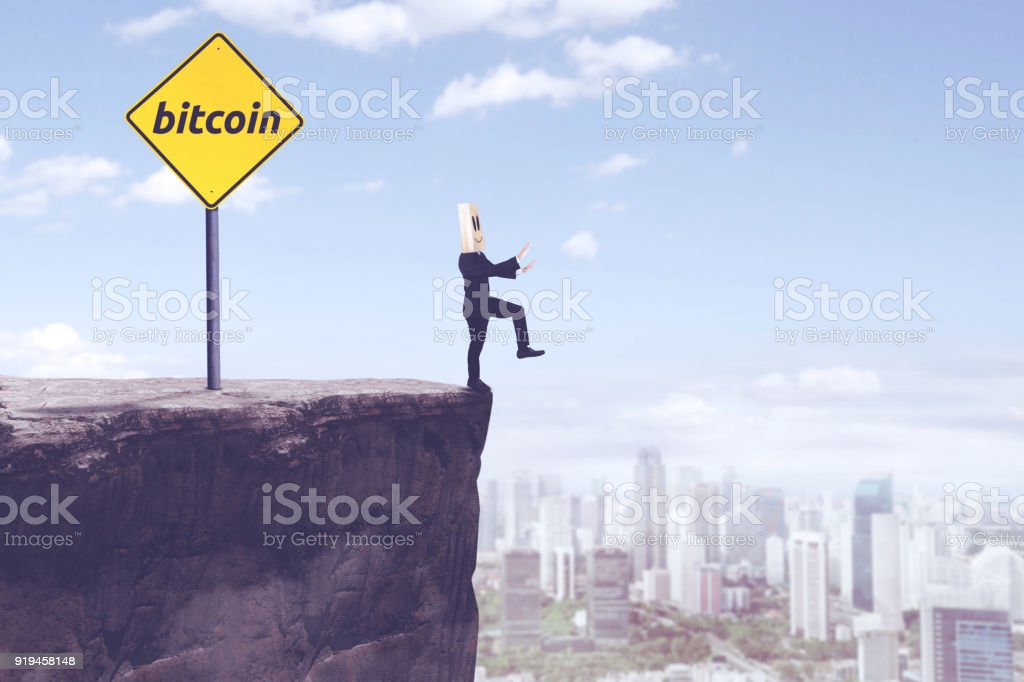 Unknown businessman with bitcoin word on cliff stock photo