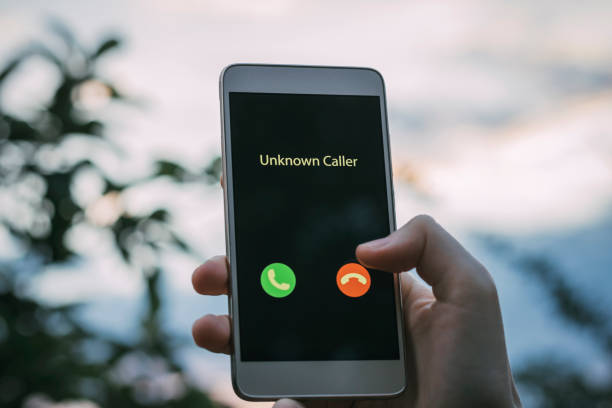 Unknown caller. A girl holds a phone in his hand and thinks to end the call. Incoming from an unknown number. Incognito or anonymous stock photo