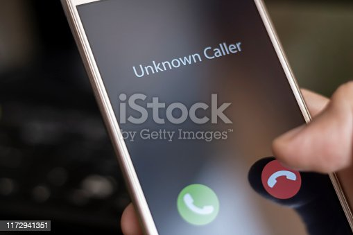 Unknown caller. A man holds a phone in his hand and thinks to end the call. Incoming from an unknown number. Incognito or anonymous