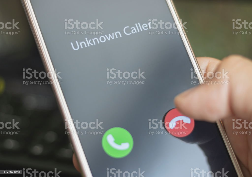 Unknown caller. A man holds a phone in his hand and thinks to end the call. Incoming from an unknown number. Incognito or anonymous Unknown caller. A man holds a phone in his hand and thinks to end the call. Incoming from an unknown number. Incognito or anonymous Adult Stock Photo