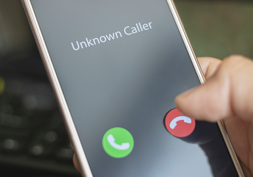 Unknown Caller A Man Holds A Phone In His Hand And Thinks To End The Call Incoming From An Unknown Number Incognito Or Anonymous Stock Photo - Download Image Now