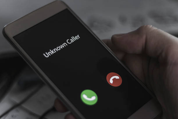 Unknown caller. A man holds a phone in his hand and thinks to end the call. Incoming from an unknown number at night. Incognito or anonymous stock photo