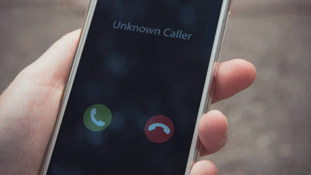 Unknown caller. A woman holds a phone in his hand outdoors in a park and thinks to end the call. Incoming from an unknown number. Incognito or anonymous stock photo