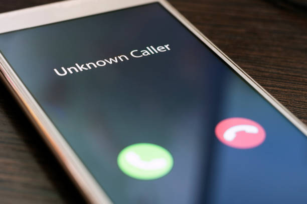 Unknown caller. Smartphone with incoming call from an unknown number at night. Incognito or anonymous stock photo