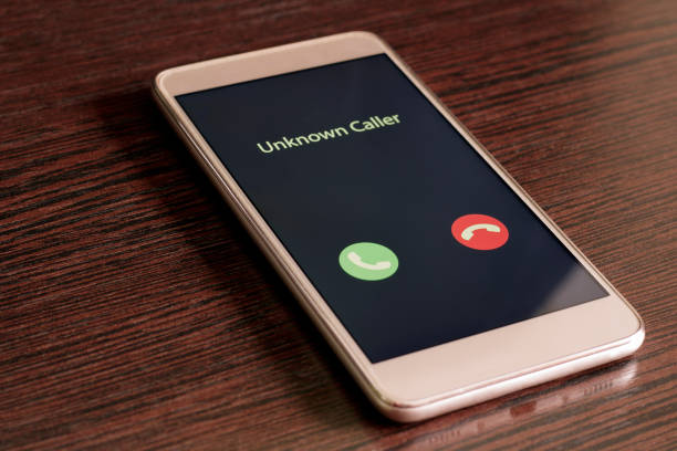 Unknown caller. White smartphone with incoming call from an unknown number on a wood table background. Incognito or anonymous stock photo