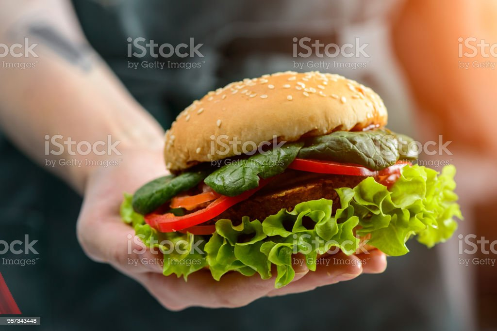 Unknown chef holding tasty veggie quinoa chickpeas burger with t stock photo