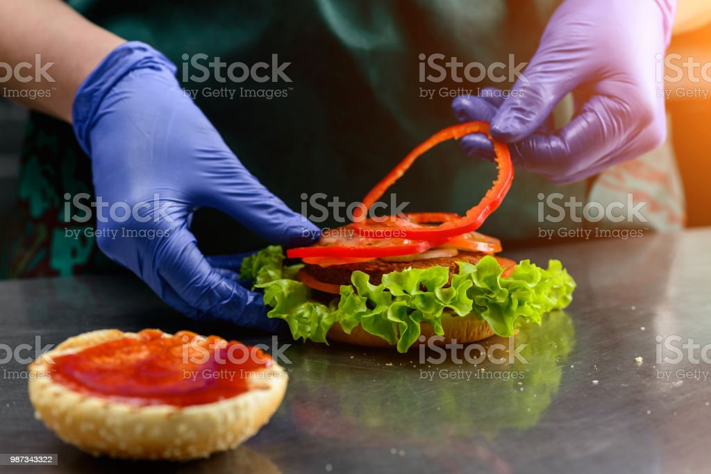 Unknown cook preparing veggie burger putting sliced tomatoes on stock photo