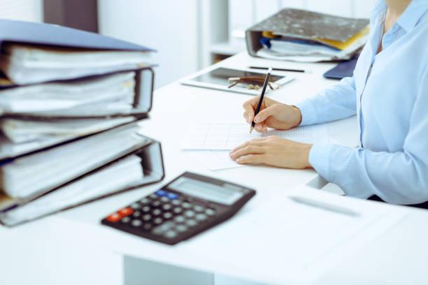 Unbekannte Buchhalterin oder Finanzinspektorin berechnet oder überprüft Das Bilanz, erstellen Bericht, Nahaufnahme. Interner Revenue Service bei der Arbeit mit Finanzdokument. Steuer- und Prüfungskonzept – Foto