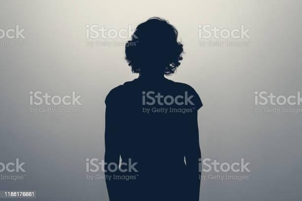 Photo of Unknown female person silhouette in studio. Concept of depression