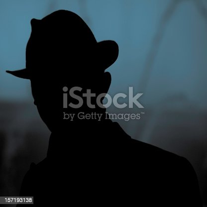 silhouette of an unknown, incognito person wearing an typical 'detective' hat, night shot. detective, police, secrecy concept