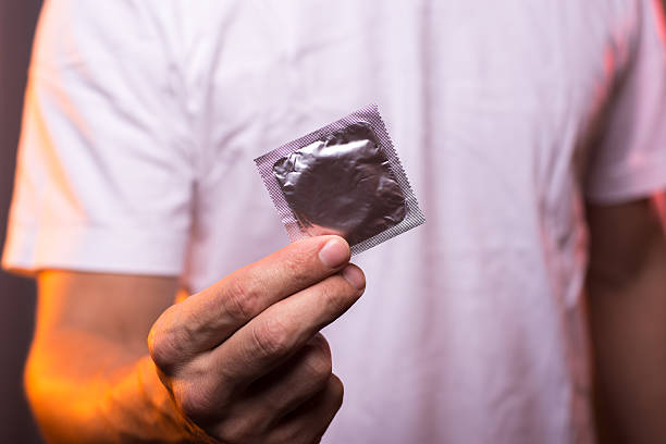 Unknown man in white shirt holding condom in hand stock photo