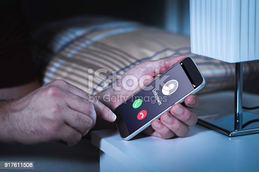 Unknown number calling in the middle of the night. Phone call from stranger. Person holding mobile and smartphone in bedroom bed home late. Unexpected call woke up.