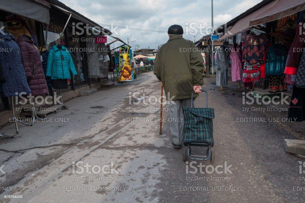 未知的老人拉袋車輪上。 免版稅 stock photo
