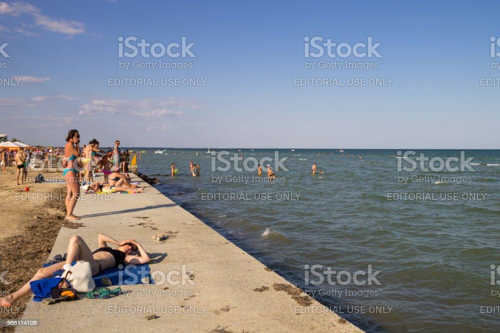 Okända människor njuta på stranden av Azovska sjön - Royaltyfri Avkoppling Bildbanksbilder
