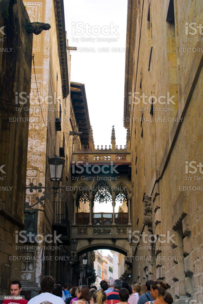 BARCELONA, SPAIN - OCTOBER 19: Unknown people in Gothic quarter. Neogothic-style bridge by architect Joan Rubió was built in 1928 over Carrer del Bisbe, near Placa del Rei and Placa Sant Jaume, in the heart of Barri Gotic. Barcelona, Catalonia, Spain. stock photo