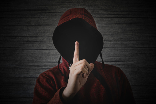 an unknown person without a face in a hood shows a finger gesture meaning towns. The concept of anonymity and secrecy in the network.