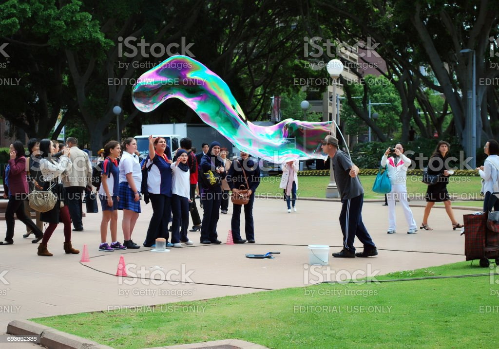 Unknown street artist makes big soap bubbles with two sticks and thread for group of females in Hyde Park stock photo