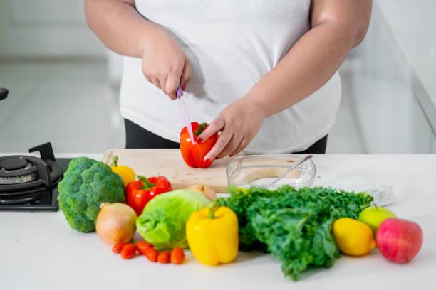 unbekannte frau eine paprika schneiden - fett nährstoff stock-fotos und bilder
