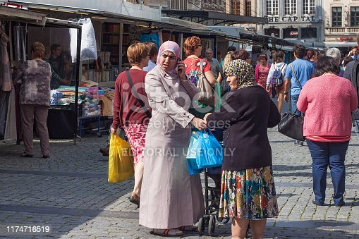 LEUVEN, BELGIUM - SEPTEMBER 05, 2014: Unknown woman dressed in an Islamic clothing standing on the Grote Markt (Main Market) in Leuven. The city is the capital of the province of Flemish Brabant.