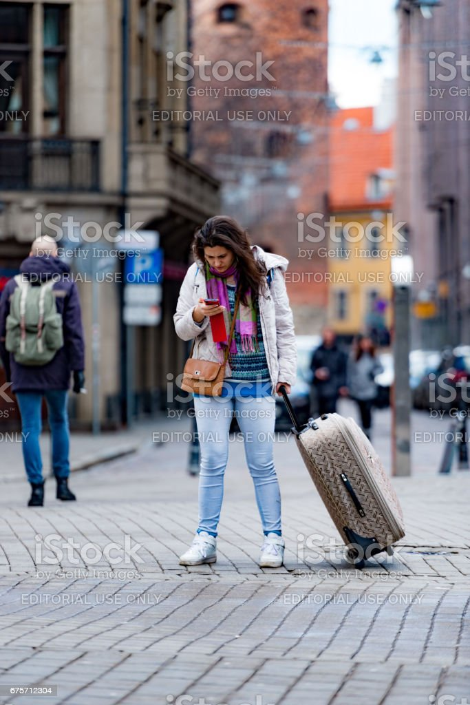 Unknown woman standing on street with luggage in hand and looks at the phone. royalty-free stock photo