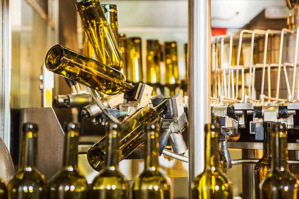 unlabeled glass bottles in bottling machine at modern winery - bottling plant stock photos and pictures