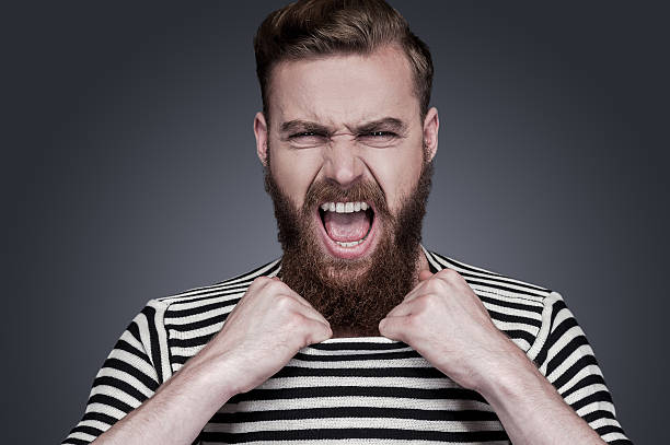 Unleashed emotions. Furious young bearded man in striped clothing stretching his collar and shouting while standing against grey background sailor suit stock pictures, royalty-free photos & images