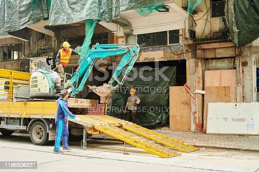 Hong Kong, Hong Kong S.A.R - April 13, 2019: three man unload an excavator from a truck in Soy Road. Mong Kok. Kowloon.