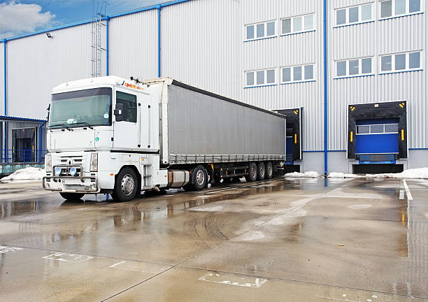 unloading big container trucks at warehouse building - lorries unloading stock photos and pictures