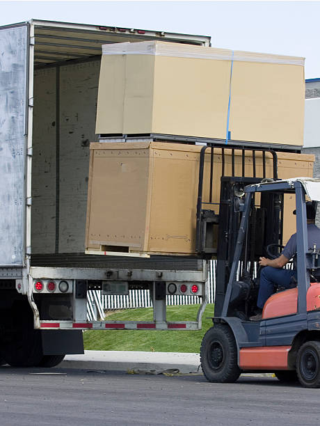 unloading large box crates, with forklift. - lorries unloading stock photos and pictures