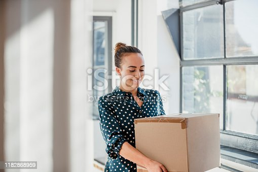Woman laughing and looking down while carrying a cardboard box at work.