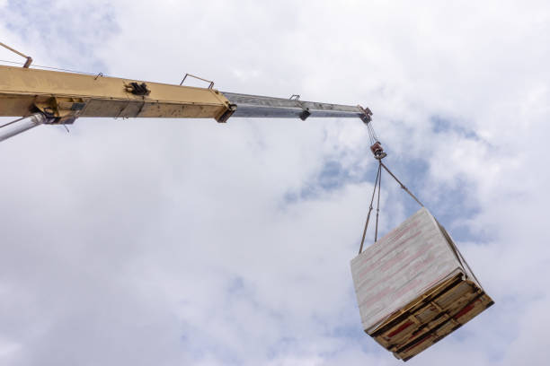 Unloading of building materials by crane at the construction site Unloading of building materials by crane at the construction site mobile crane stock pictures, royalty-free photos & images