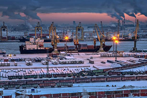 Unloading of cargo ship in sea port winter evening. stock photo
