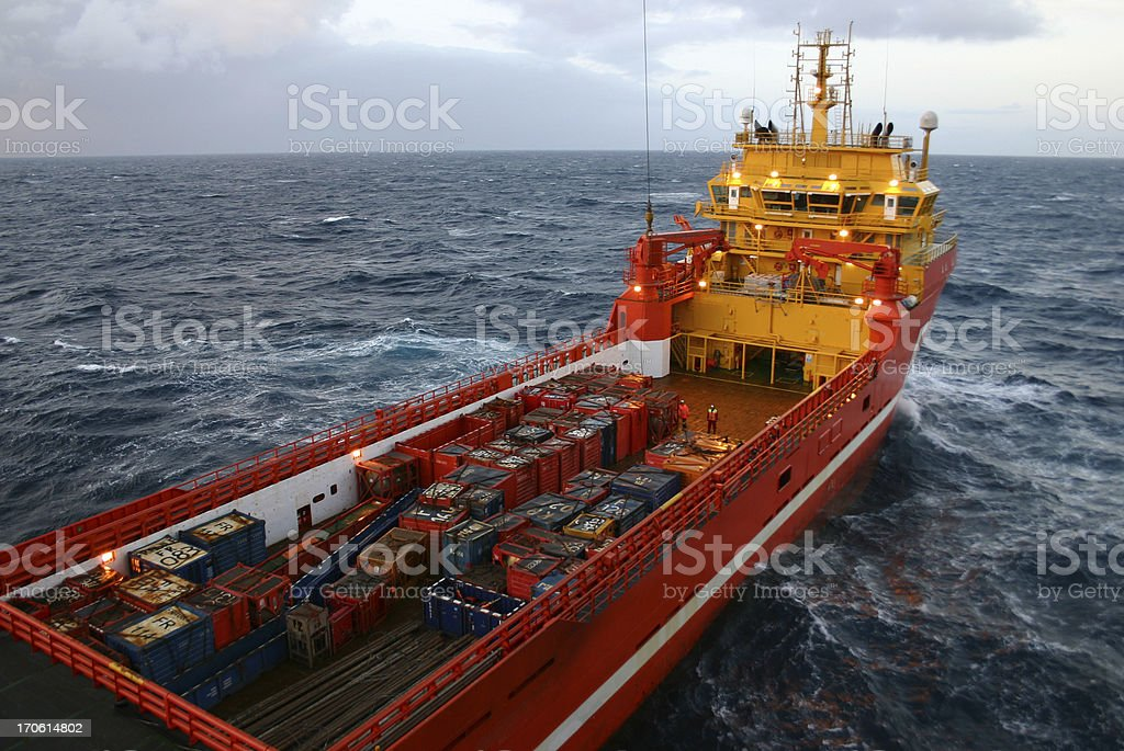 unloading supplies from boat to oil rig offshore royalty-free stock photo