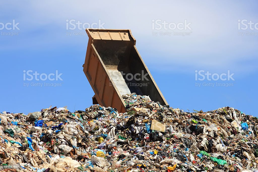 unloading truck in a mountain of trash stock photo