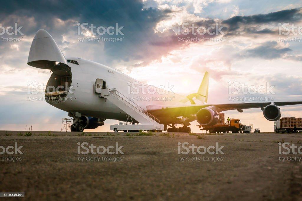 Unloading wide body transport cargo plane in the morning sun стоковое фото