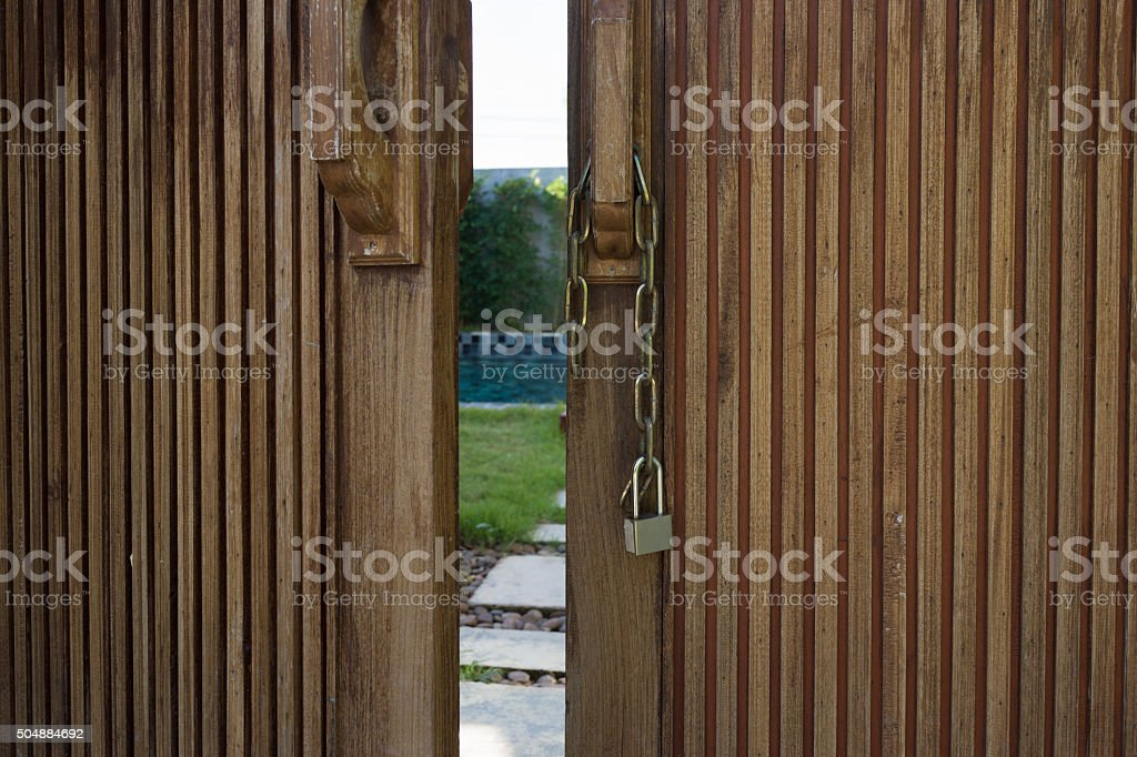 Unlocked metal chain on wooden doors with garden behind stock photo