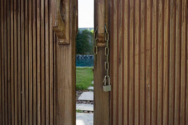 Unlocked metal chain on wooden doors with garden behind stock photo