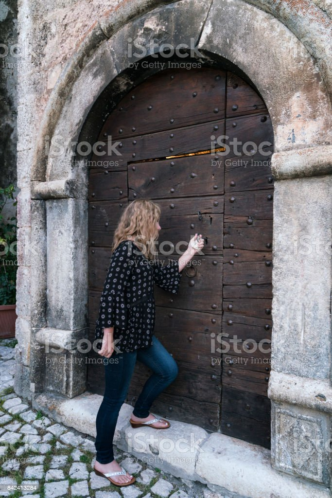 Unlocking a massive medieval door stock photo