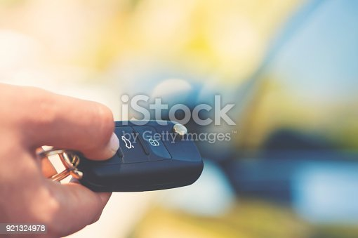 Unlocking car with car key. Tight crop with part of woman's hand. The car is out of focus in the background
