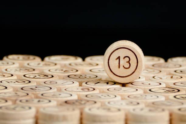 unglückszahl 13 im holzfass-lotto. schwarzer hintergrund. nahaufnahme - number 13 stock-fotos und bilder