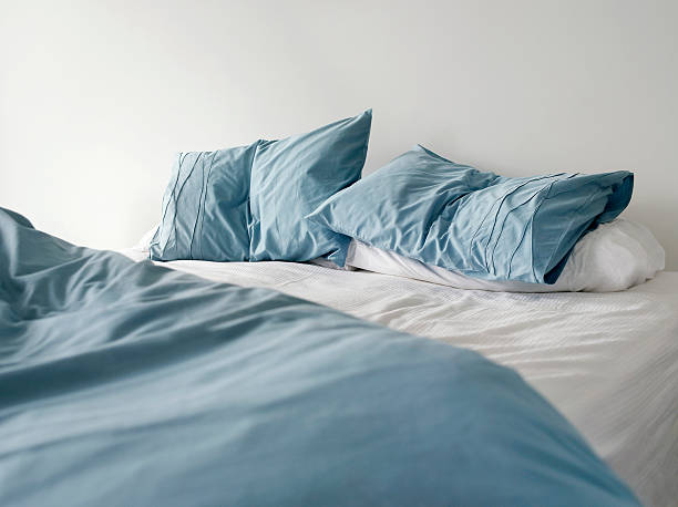 unmade bed with crumpled blue linens stock photo