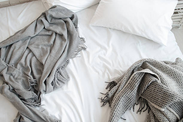 Unmade bed with pillow and gray blankets top view stock photo