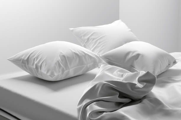 Unmade bed with soft clean white linen and pillows stock photo