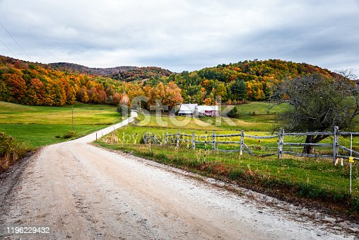 488912426istockphoto Unmade road to a farm at the foot of hills covered in colourful trees at the peak of autumn foliage 1196229432