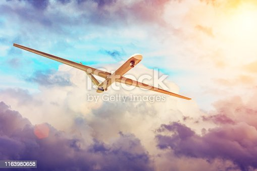 535194869 istock photo Unmanned military aircraft drone flies the at sunset clouds sky. 1163980658