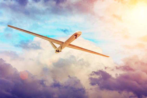 無人軍用機ドローンは、夕日雲の空を飛びます。 - リモート ストックフォトと画像
