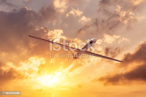 535194869 istock photo Unmanned military drone flies the at sunset clouds sky. 1160053090